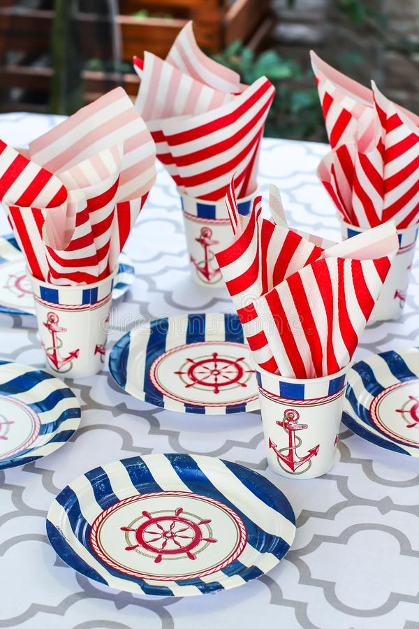 Table serving setting in a marine style. Sea decor. Festive table. Sea theme. Plates, cups and napkins with a sea anchor. And a ship steering wheel royalty free stock images