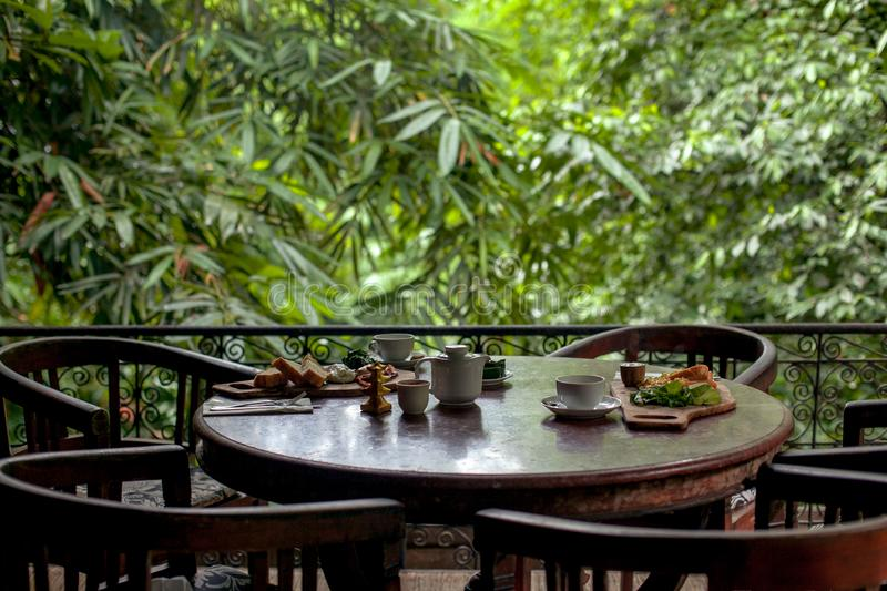 Table set for breakfast at cozy restaurant on greenery terrace in Bali style royalty free stock photography