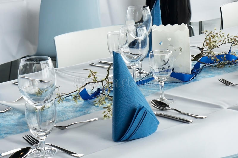 Table set for dinner party. In white and blue royalty free stock photo