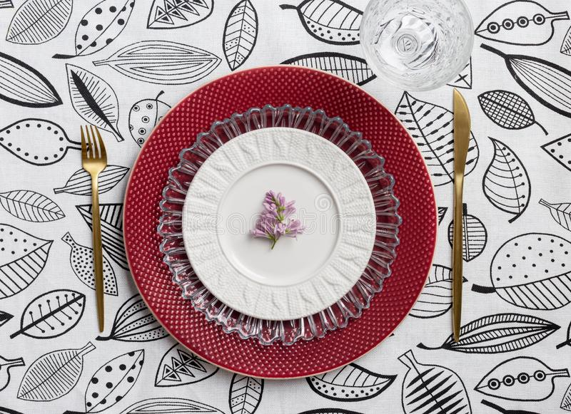 Table set with red plate and gold table ware stock photography
