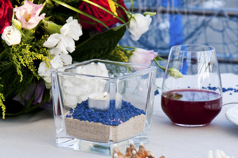 Table set by the sea with glass of wine and candle stock photo