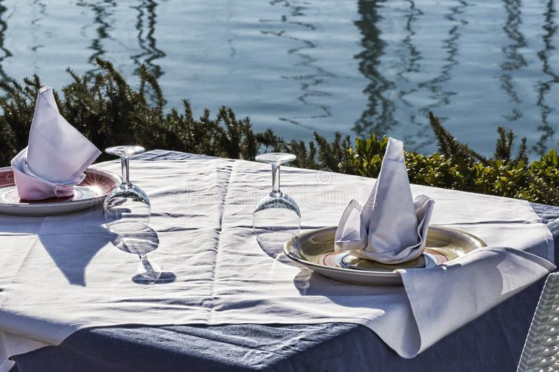 Table set by the sea with white tablecloth, wine glasses, well-folded napkins and porcelain dishes. Table set by the sea with white tablecloth, wine glasses stock photo