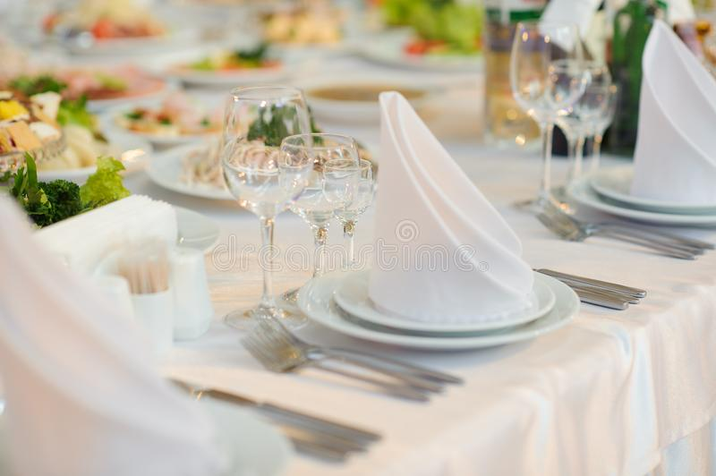 Table set service with silverware and glass stemware at restaurant before party. Appetizer, arrangement, cheese, cup, drink, energy, food, dinner, formal stock photography