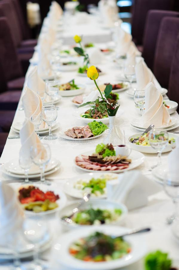 Table set service with silverware and glass stemware at restaurant before party. Appetizer, arrangement, cheese, cup, drink, energy, food, dinner, formal royalty free stock images
