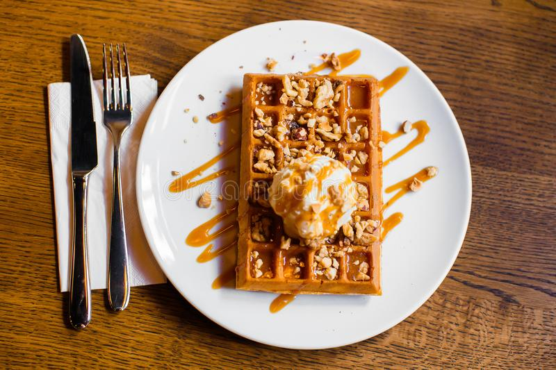The table set. The tasty composition of the belgian waffles with white ice cream decorated with caramel and nuts. stock photos