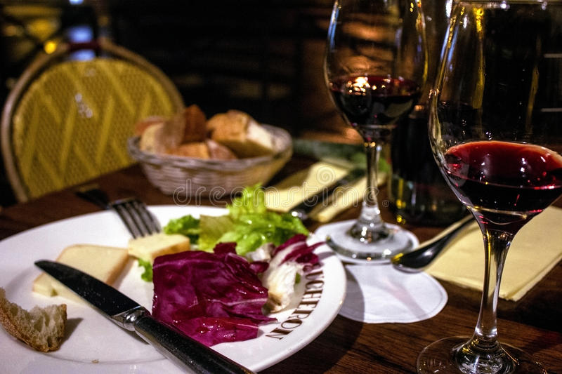 A table is set with wine, cheese, and bread. A french cafe table is set with wine, cheese, and bread stock photos