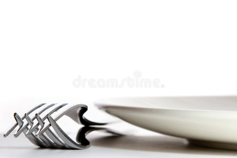 Table Setting. Low angle view of two forks and a plate on a table
