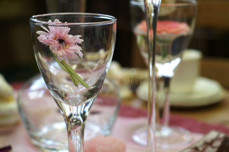 Table setting. With glass and a pink flower in it stock images