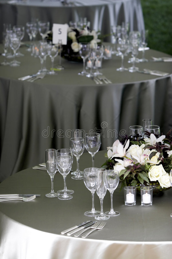 Table setting for a banquet or event. A typical dinner table setting, with a shallow depth of field with the focus on the forground table, with the other tables royalty free stock photography