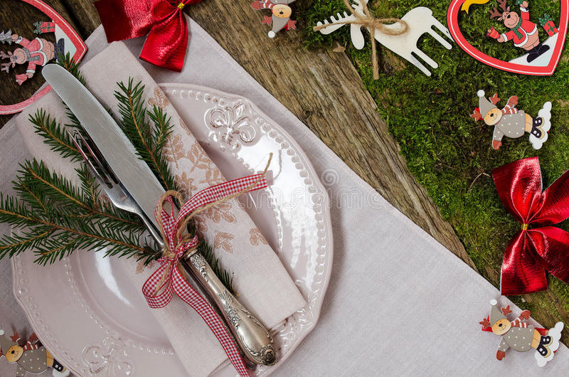 Table setting for Christmas. Vintage style. Plate, napkin, Cutlery. A sprig of spruce. decorative tape. The old Board and moss. Table setting. Christmas royalty free stock images