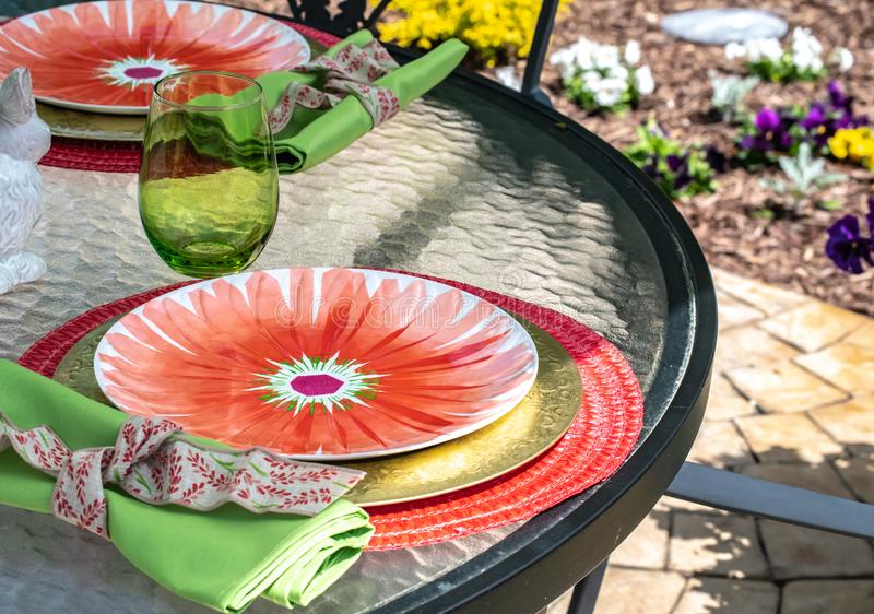 Patio Dining-Place setting with red, green, and flower design on plate. Summer entertaining at home, event, ideas. stock photography