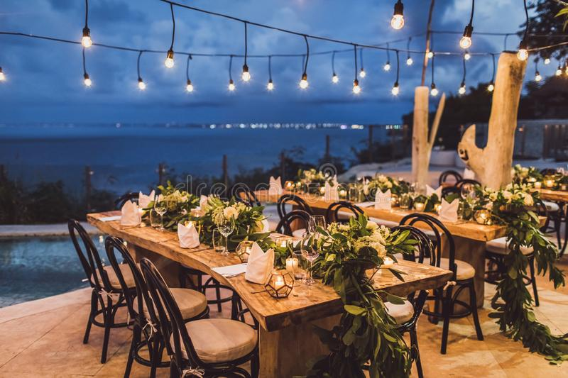 Table setting decoration at night wedding ceremony. Table setting at night wedding ceremony. Decoration with fresh flowers, candles, light bulbs, garlands royalty free stock images