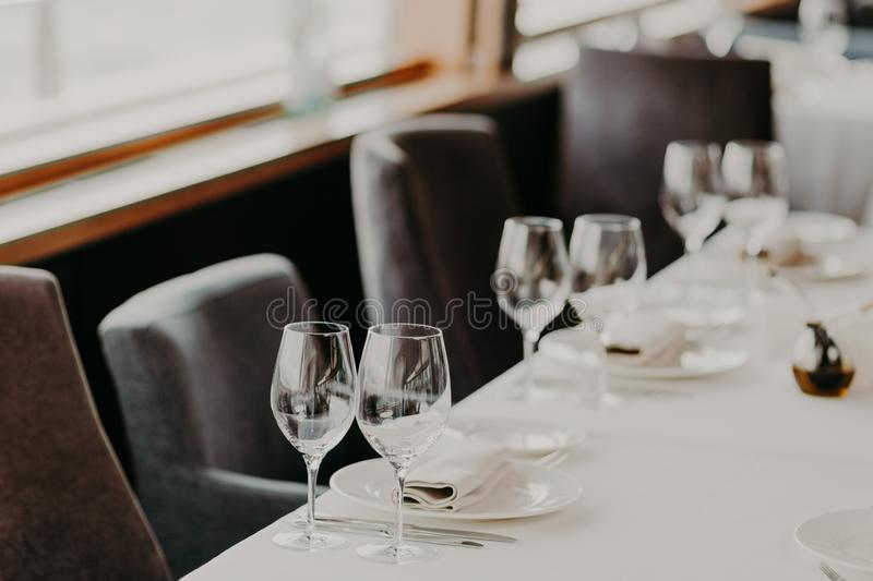 Table setting for dining. Beautiful served table for dinner or supper for special Occasion. White tableclothes. Empty dishes. Cozy royalty free stock images