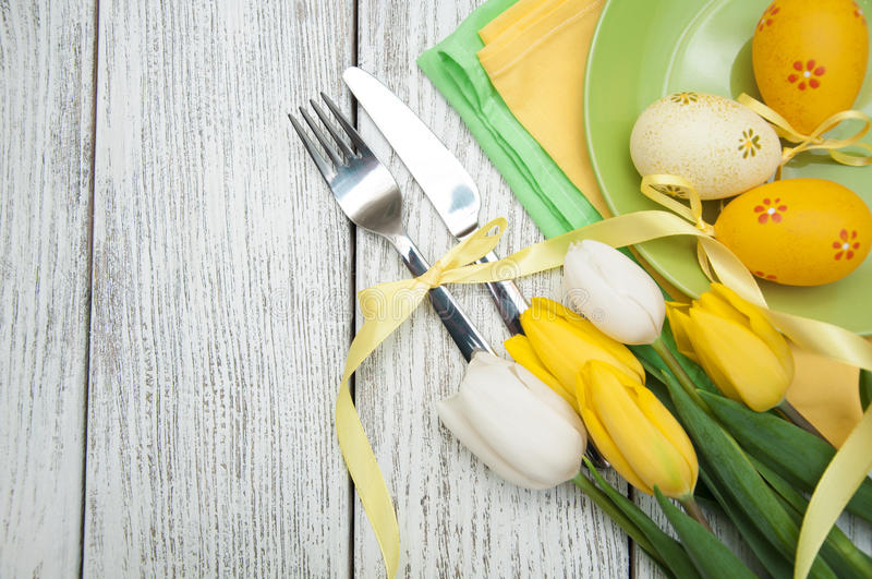 Table setting. Easter background with yellow tulips and colorful eggs over white wooden table. Top view with copy space royalty free stock photography