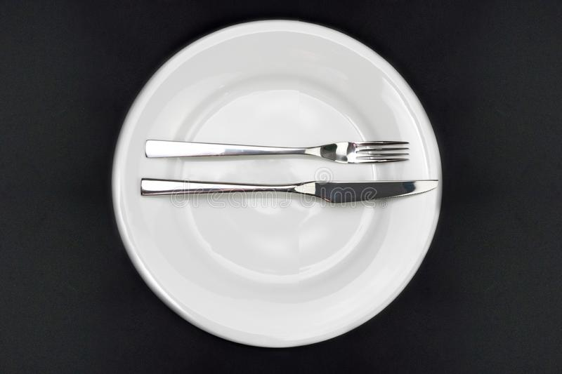 Table setting. Empty plate, knife and fork on a black background. I liked the dish. Top view and flat lay with copy space royalty free stock photos