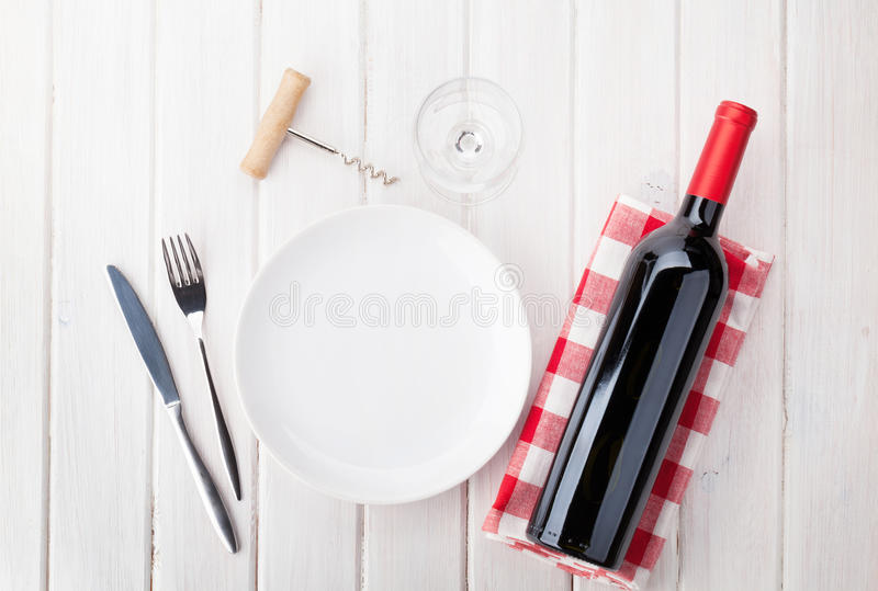Table setting with empty plate, wine glass and red wine bottle royalty free stock images