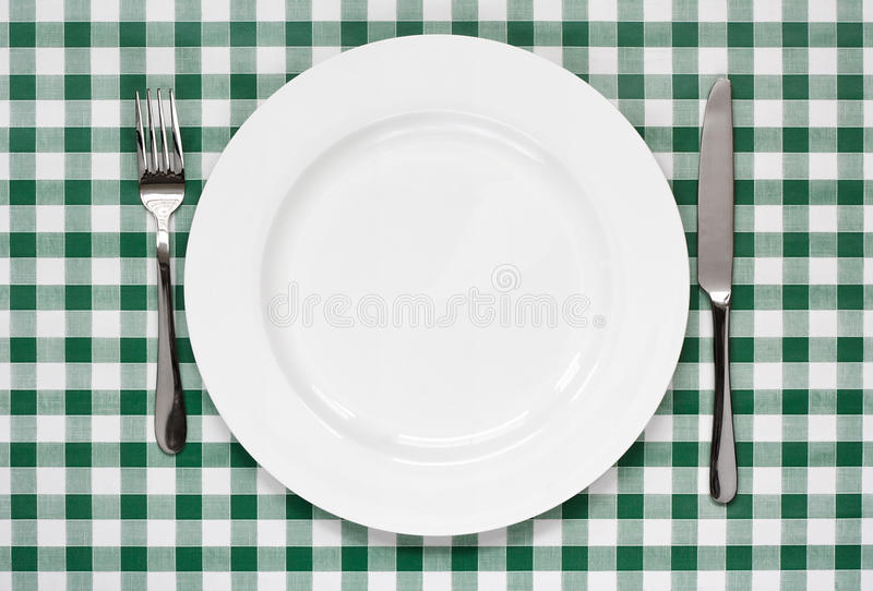 Table setting on green Gingham tablecoth. Place setting with empty plate, knife and fork on green gingham background popular symbol for diners and cafes royalty free stock images