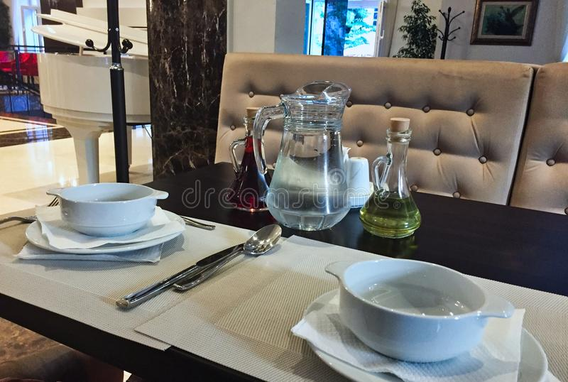 Table Setting in Hotel Restaurant. Table setting including soup bowls, cutlery, olive oil and wine vinegar, in a hotel dining room stock photography