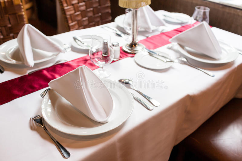 Table setting for a lovey dinner. Empty glasses set in restaurant. Part of interior. napkins, plates, and cutlery. royalty free stock images