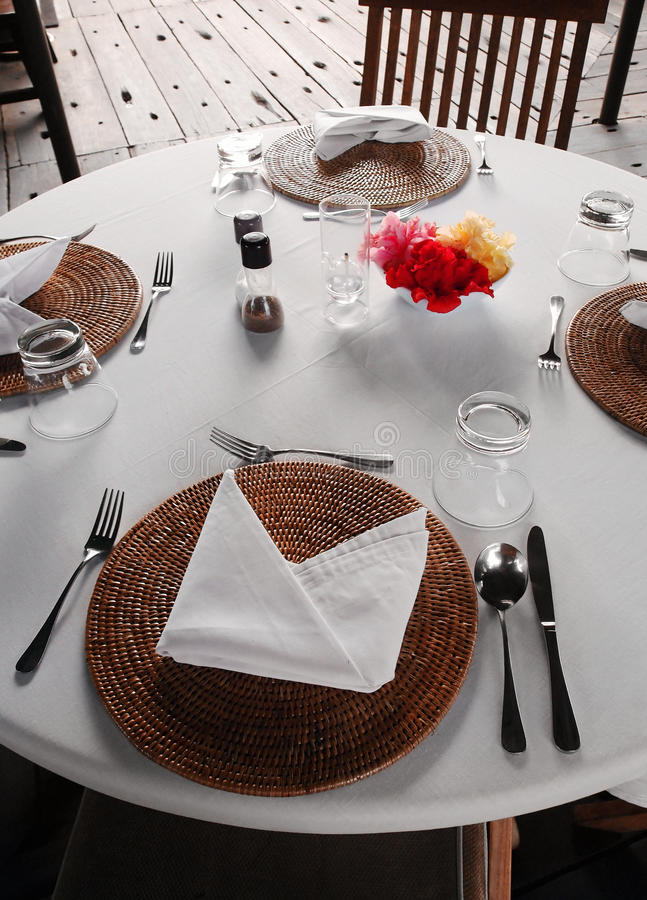 Table setting, outdoor dining patio area. A photograph showing the table setting style of an outdoors wood deck patio dining area in a tropical resort hotel stock photos