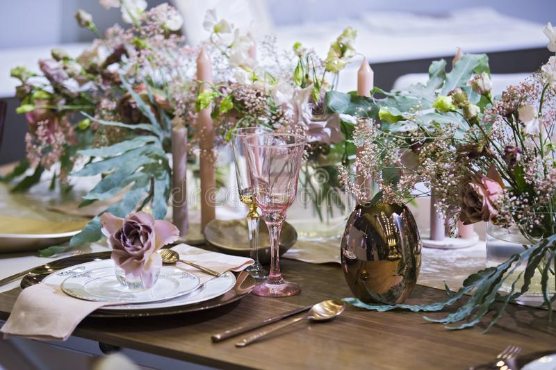 Table setting in pink color, for a wedding or other event, wine glasses, plates, spoons, forks, flowers and vases royalty free stock photography