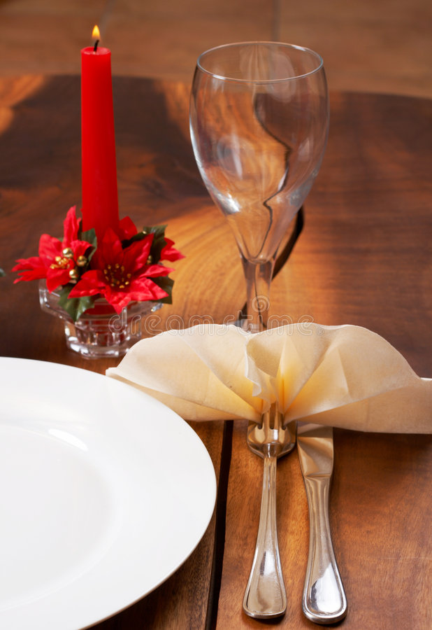 Table setting with a plate and cutlery. Table setting with a white plate, cutlery, burning candle and empty wine glass stock photo