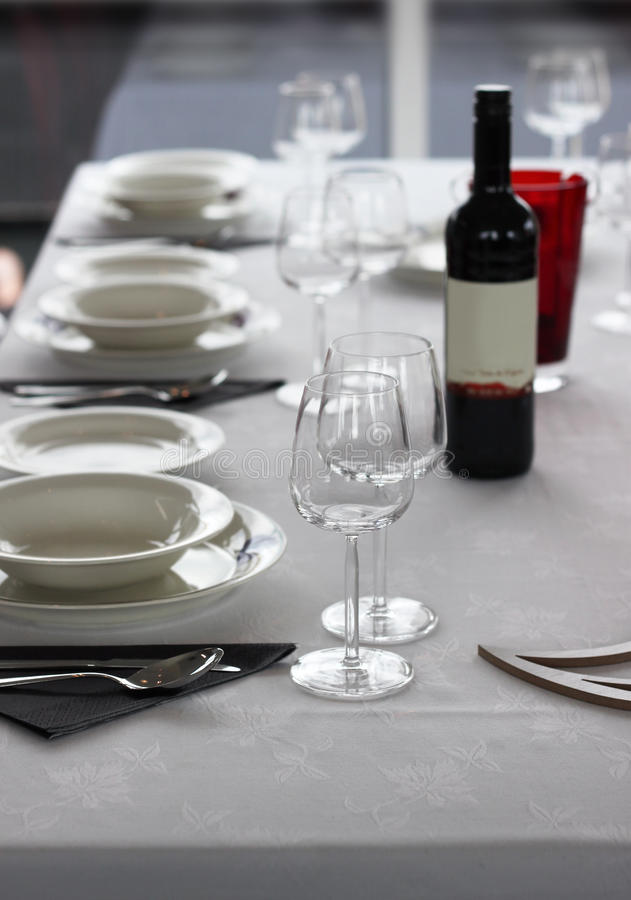 Table setting with plates and wine glasses stock images