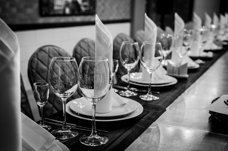 Black and white photography. Empty glasses in restaurant royalty free stock photography