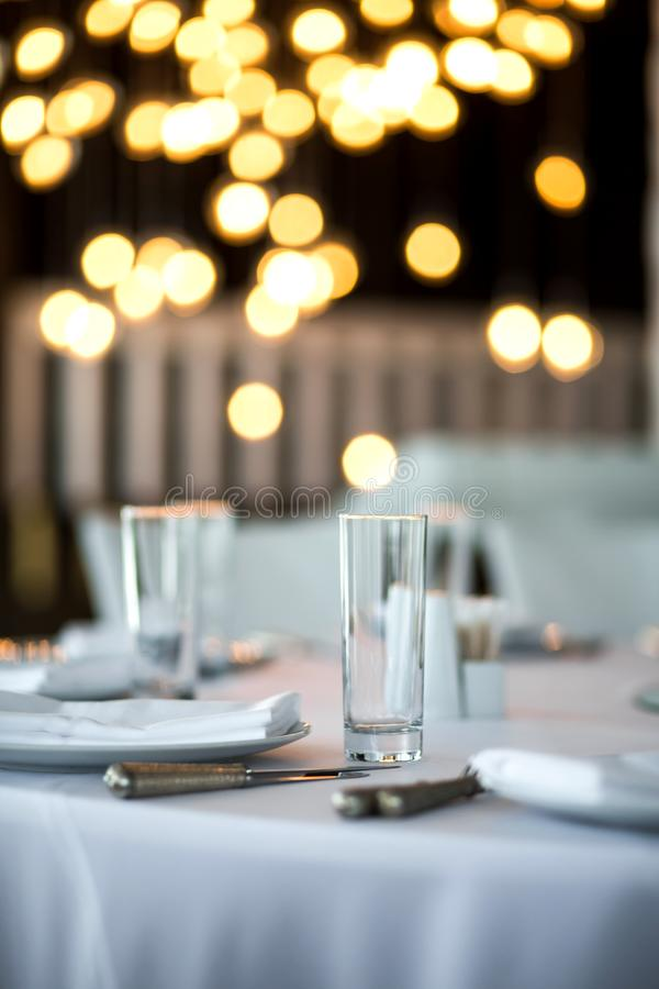 Table setting at a restaurant. Clean glass cup close up. Details of the banquet table. On the background blur are burning garlands. With light bulbs royalty free stock photo