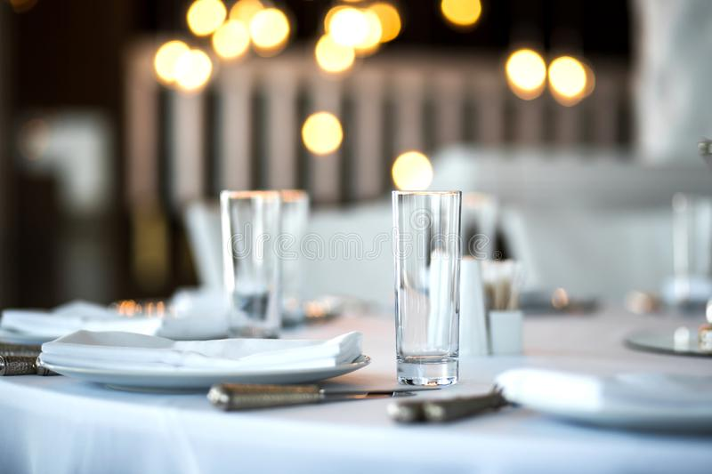 Table setting at a restaurant. Clean glass cup close up. Details of the banquet table. On the background blur are burning garlands. With light bulbs royalty free stock images