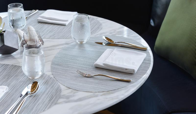Table setting in the restaurant. Decorated elegant table, glasses, napkin, knife, fork and spoon stock photo