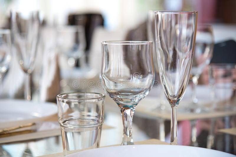 Table setting in the restaurant, including glasses for wine, champagne and cognac, napkins and plates for guests royalty free stock photos