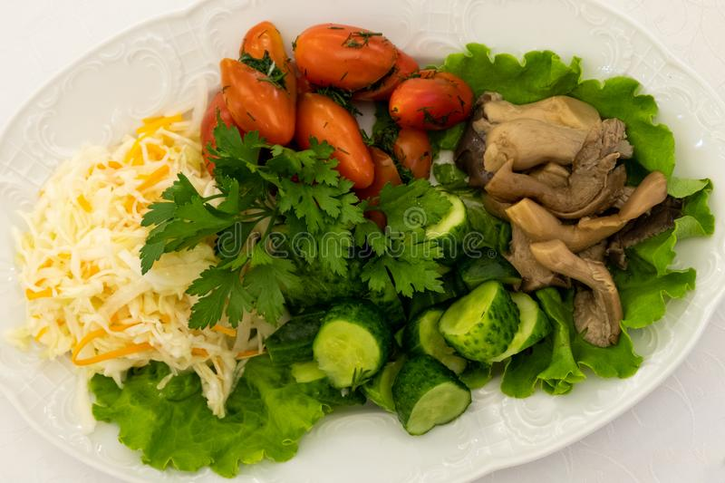 Table setting in a restaurant. Dish from the menu with cold snacks. Sauerkraut, mushrooms, tomatoes, cucumbers, lettuce stock photos