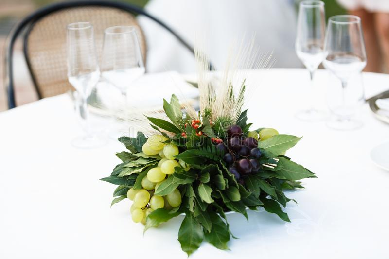 Table setting for a romantic dinner. Bouquet with bunches of grapes ,laurel leaves stock photography