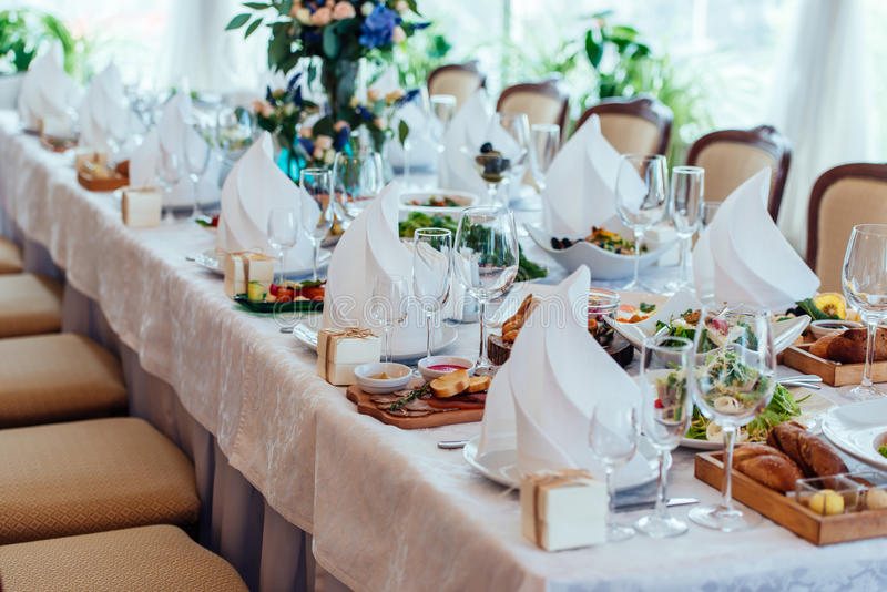 Table setting. Table served for wedding banquet, close up view. White napkin on a white empty plate on dining table. Table setting. Table served for wedding stock image