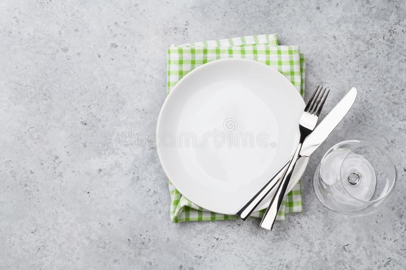 Table setting. Empty plate, knife, fork, wine glass and napkin. Top view and flat lay with copy space royalty free stock photo