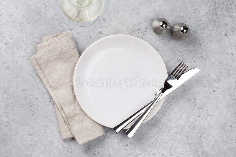 Table setting. Empty plate, knife, fork, wine glass and napkin. Top view and flat lay with copy space stock photo