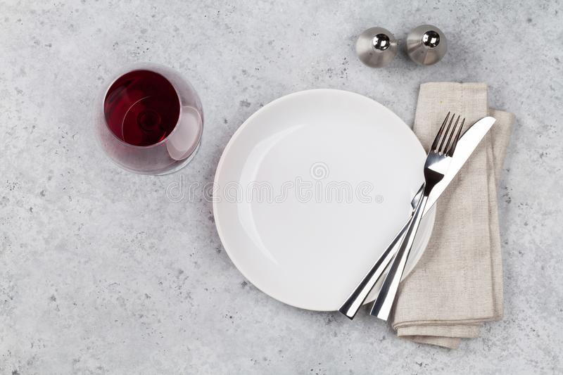 Table setting. Empty plate, knife, fork, wine glass and napkin. Top view and flat lay with copy space stock image
