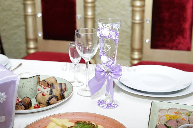 table setting for a wedding, crystal glass decorated with beads with rhinestones and satin ribbons, glasses, plates, food. royalty free stock photos