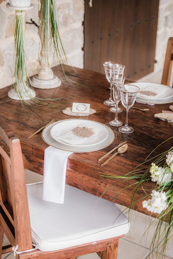 Table setting at wedding. In Ibiza showing plates, starter in small white dish, white napkin, wine glasses, candlesticks and white flowers stock photography