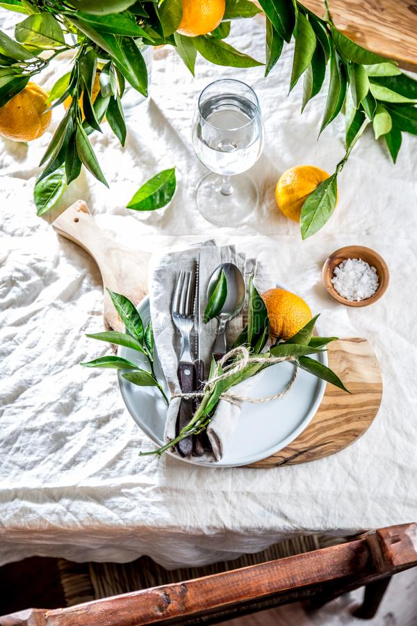 Table setting with white plate, cutlery, linen napkin and orange tree branch decoration on white linen tablecloth royalty free stock photography