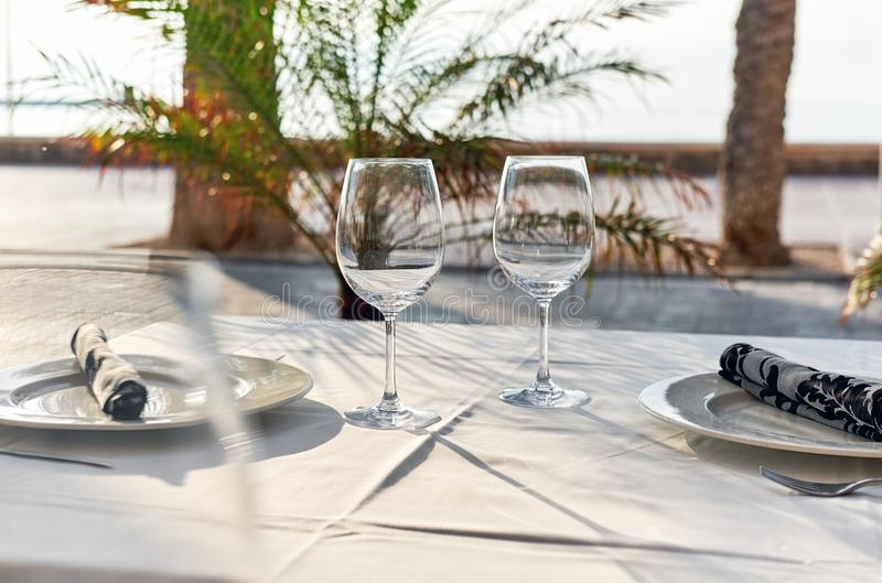 Table setting with a wine glasses, cutlery and plates stock images