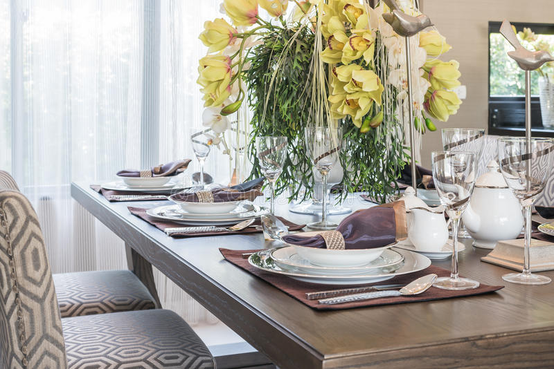 Table setting on wooden dinning room with vase of flower royalty free stock image