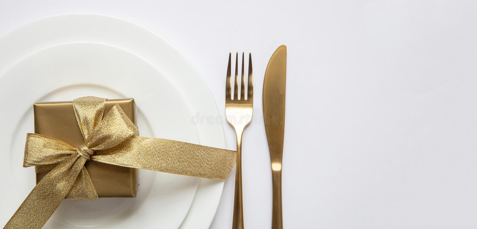 Table setting, xmas, new year. Gold cutlery on white set of dishes, white background stock images