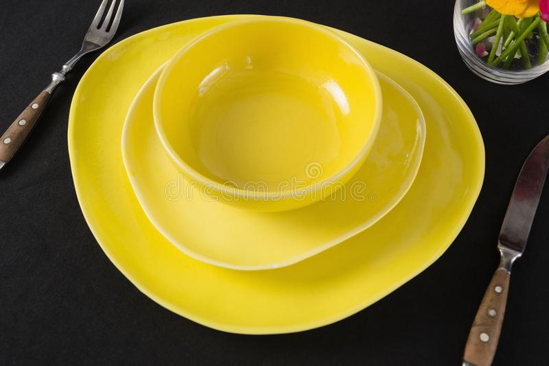 Table setting with yellow bowl and plates. Close-up of table setting with yellow bowl and plates royalty free stock photography