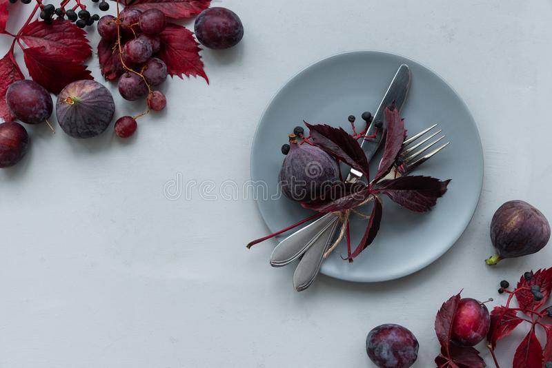 Table settings, purple girlish wild grape leaves, grapes, plums and figs on gray wooden background. Top view. Flat lay. Autumn royalty free stock photography