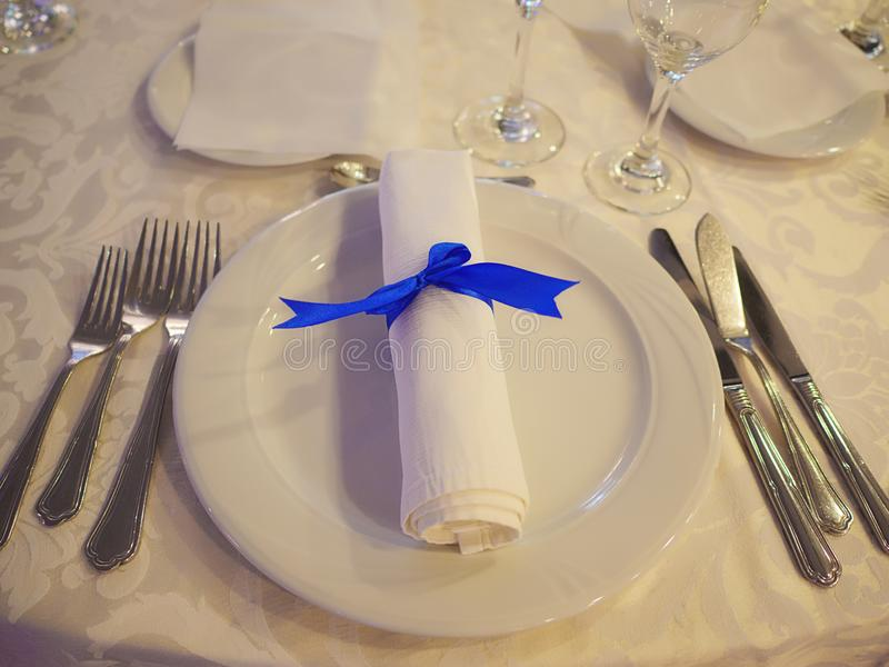 Table setup with silverware placed in the order of use, napkin and white china. Simple table setting for formal event, elegant dining or a wedding, ready for royalty free stock image