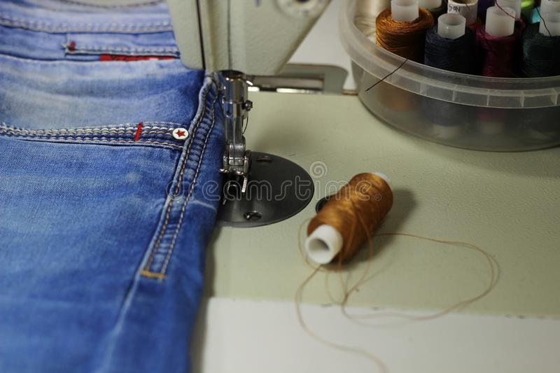 On the table of the sewing machine lie denim fabrics, close-up, stock image