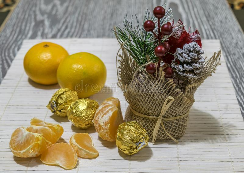 On the table are slices of mandarin, candy and Christmas decoration. stock image