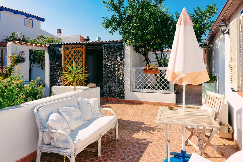 Table and sofa at porch in Costa Smeralda. Luxury resort in Sardinia Island in Italy in summer. Cozy veranda with chair and umbrella in Sardinian town in royalty free stock photos